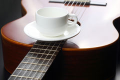 Empty white cup lying on the acoustic guitar