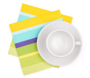 Empty white cup on placemat. Empty white cup on color placemat. Isolated on white background Stock Photos
