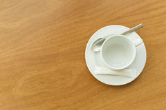 Empty white cup and saucer with a silver spoon and as ache of sugar on a wooden table Royalty Free Stock Photos