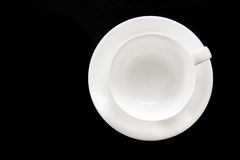 Empty white cup with stand. On the black background stock photography