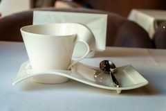 Empty white Cup on a white plate of unusual form with teaspoon. In the cafe Stock Photography