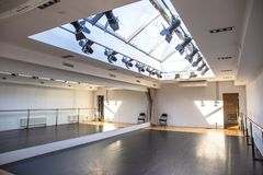 Empty white dance studio or hall for activities or yoga room with mirror wall and windows in celling.  royalty free stock photo