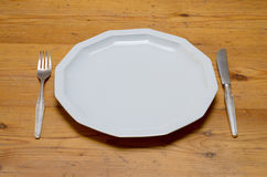 Empty white dinner plate with knife and fork Royalty Free Stock Images
