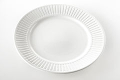 Empty white dinner plate with ridged rim. Empty round white dinner plate with a ridged rim pattern on a white background with space for food or product placement Stock Images