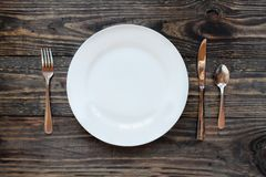 Empty White Dinner Plate Shot from Above. Empty white dinner plate over a rustic wooden table / background with fork, knife and spoon.. Top view royalty free stock image