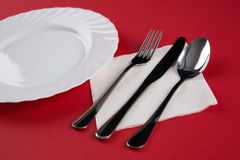 Empty white dinner plate with silver fork and Dessert Tablespoon, isolated on red tablecloth background with copy space. Table Set Stock Photos