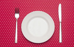 Empty white dinner plate. With utensils on fun red polka dot tablecloth Royalty Free Stock Photos