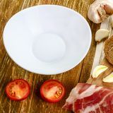 Empty white dish and bread, tomatoes, bacon and garlic. On woode. N background. Square. Close-up Stock Images
