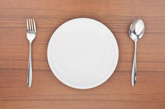 Empty white dish, spoon and fork. On wood table Royalty Free Stock Image