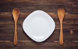 Empty white dish with wooden spoons  on dark wooden background. Top view Stock Image