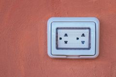 Empty white dual electric outlet with plastic waterproof setup on brown clay wall. royalty free stock image