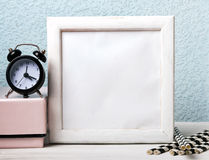 Empty white frame, black clock and paper straws Royalty Free Stock Photography