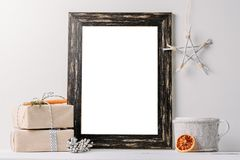 Empty white frame mock up. Black wooden frame mockup with christmas decorations on a white background stock photo
