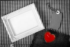 Empty white frame next red heart sign from candle and paper tag Royalty Free Stock Photo