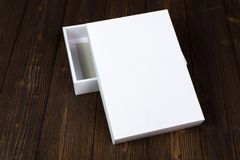Empty white gift box or tray for mock up on dark wooden table wi Royalty Free Stock Photo