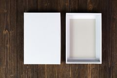 Empty white gift box or tray for mock up on dark wooden table wi Stock Photography