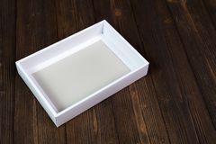 Empty white gift box or tray for mock up on dark wooden table wi Royalty Free Stock Image