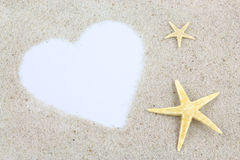 Empty white heart and starfishes on the beach Royalty Free Stock Photo