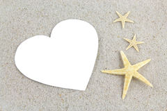 Empty white heart and starfishes on the beach Stock Photo