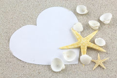 Empty white heart and starfishes on the beach Stock Images