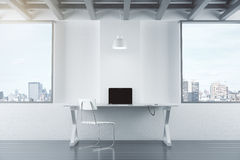 Empty white interior with table, chair, brick wall and windows,. And laptop royalty free stock image