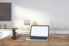 Empty white laptop on kitchen counter. Close up of empty white laptop on wooden kitchen counter with blurry interior in the background. Web advertisement concept stock image