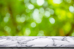 Empty white marble table on green bokeh background. Royalty Free Stock Photography