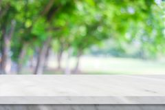 Empty white marble table over blur green nature park background, product display montage royalty free stock photography