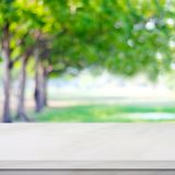 Empty white marble table over blur green park background. Product display montage Stock Photos