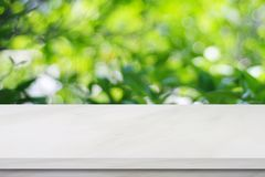 Empty white marble table over blur green tree leaves background, Royalty Free Stock Photos