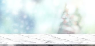 Empty white marble table top with abstract muted blur christmas. Tree and snow fall background with bokeh light,Holiday backdrop,Mock up banner for display or stock image