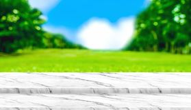 Empty white marble table top with blur grass field in park with. Bokeh light at background,Mock up template for display of your design,Banner for advertise of Stock Photography