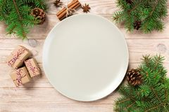 Empty white matte plate on wooden background with christmas decoration, Round dish. New Year concept.  royalty free stock image