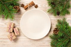 Empty white matte plate on wooden background. with christmas decoration, Round dish. New Year concept.  stock photography
