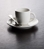 Empty White Mug on Saucer with Spoon. Close Up of Empty White Mug on Saucer with Silver Spoon on Dark Wooden Table with Visible Wood Grain Stock Image