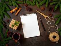 Empty white notebook and pen on dark black Christmas background of fir branches, cones, gifts. Letter, mock up. Empty white notebook and pen on a dark black Royalty Free Stock Image