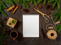Empty white notebook and pen on dark black Christmas background of fir branches, cones, gifts. Letter, mock up. Empty white notebook and pen on a dark black Stock Images