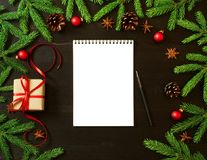 Empty white notebook and pen on dark black Christmas background of fir branches, cones, gifts. Letter, mock up. Copy space Royalty Free Stock Image