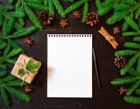 Empty white notebook and pen on dark black Christmas background of fir branches, cones, gifts. Letter, mock up. Empty white notebook and pen on a dark black Stock Image
