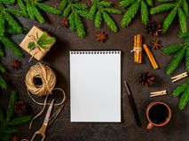 Empty white notebook and pen on dark black Christmas background of fir branches, cones, gifts. Letter, mock up. Empty white notebook and pen on a dark black royalty free stock photography
