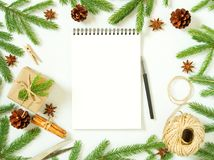 Empty white notebook and pen on white Christmas background of fir branches, cones, gifts. Letter To Santa Claus, mock up. Empty white notebook and pen on a white Stock Image