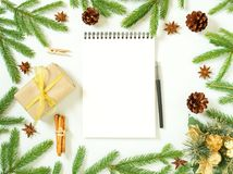 Empty white notebook and pen on white Christmas background of fir branches, cones, gifts. Letter To Santa Claus, mock up. Empty white notebook and pen on a white Stock Photo