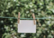 Empty white paper hanged with clothes pegs on rope at garden. An empty white paper hanged with clothes pegs on rope at garden Stock Photo