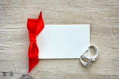 Empty white paper label, red ribbon, two silver hearts Royalty Free Stock Photos