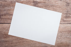 Empty white paper on wooden table top view Royalty Free Stock Photo