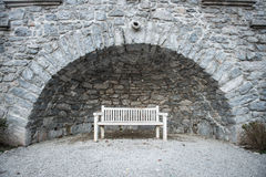 Empty white park bench under stone bridge Stock Image