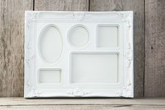 Empty white picture frame on wooden background. stock photos