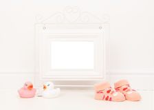 Empty white picture frame with space for text or wishes in a white living room setting with pink baby sock and pink and white rubb. Er ducks royalty free stock photos