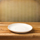 Empty white plate. On wooden table over grunge striped wallpaper Royalty Free Stock Photography