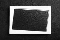 Empty white plate with black stone surface Stock Photo